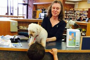Children pet a dog at Paws to Read