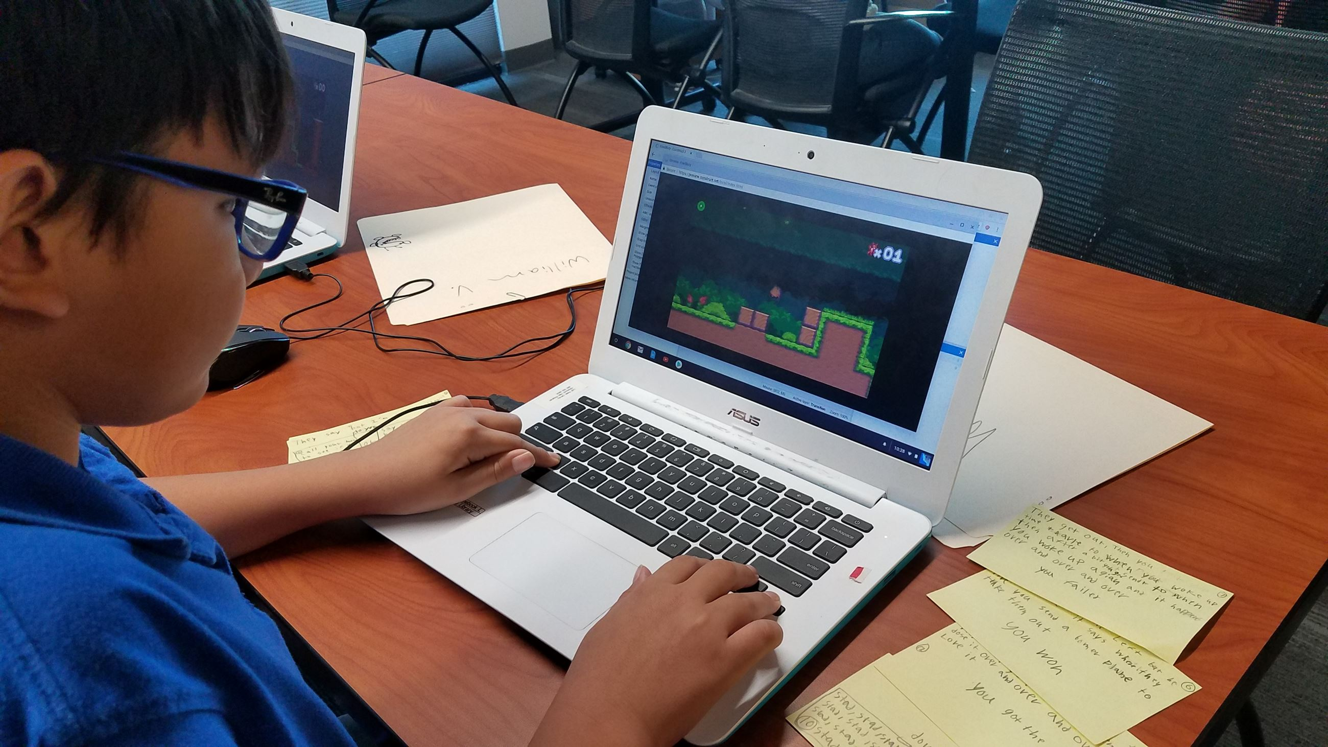 A middle school age boy sits at a computer designing a video game